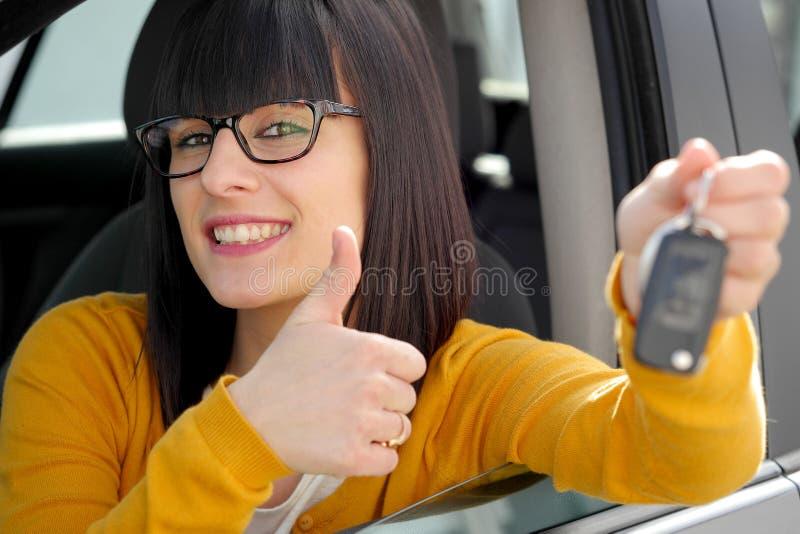 Mulher feliz nova que mostra a chave do carro novo fotos de stock