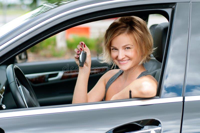 Mulher feliz nova que mostra a chave do carro novo imagens de stock royalty free