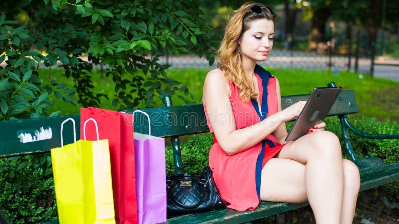 Mulher feliz nova que senta-se em um banco com sacos de compras e a tabuleta coloridos. fotos de stock
