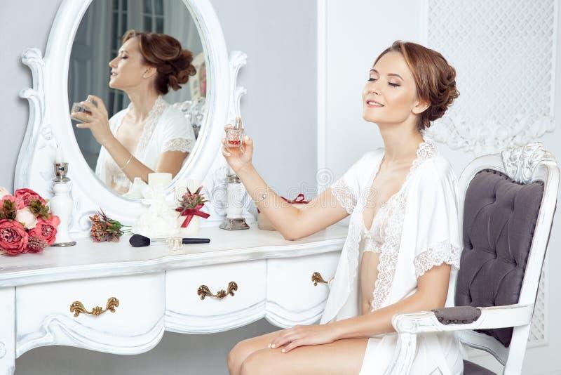 Mulher feliz nova que senta-se na frente do espelho e que prepara-se nós fotos de stock
