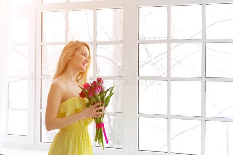 Mulher feliz nova que sorri com grupo da tulipa no vestido amarelo foto de stock