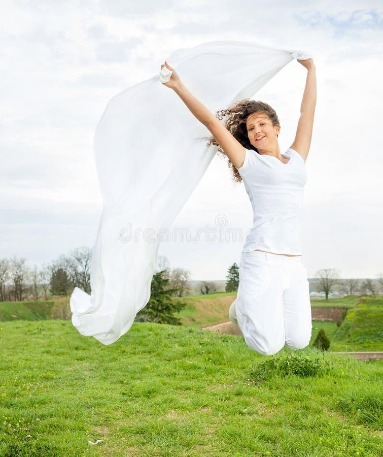 A mulher feliz nova salta e guardando uma parte de pano branca no th imagem de stock royalty free