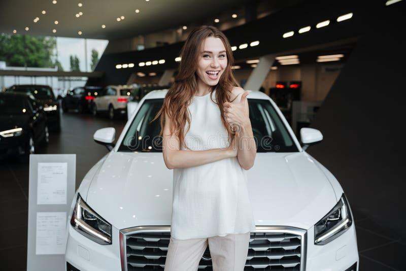 Mulher feliz nova surpreendente que está o carro próximo fotografia de stock