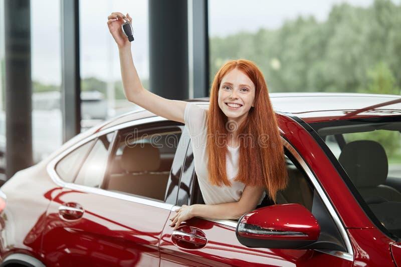 Mulher feliz nova surpreendida por um carro novo na sala de exposições do carro, presente de seu marido fotografia de stock royalty free