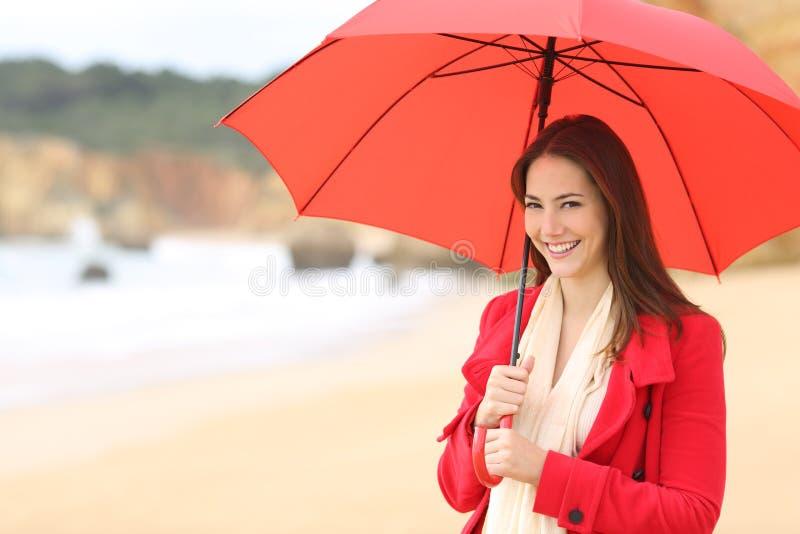 A mulher feliz olha a câmera que guarda um guarda-chuva vermelho foto de stock royalty free