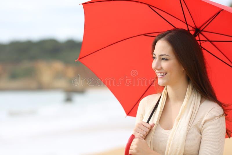 A mulher feliz olha o lado que guarda o guarda-chuva vermelho na praia imagens de stock