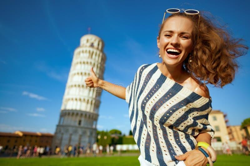 Mulher feliz perto da torre de lente em Pisa, Itália mostrando polegares para cima imagem de stock