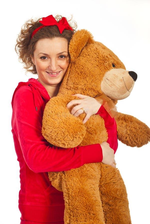 Mulher feliz que abraça o urso de peluche grande fotografia de stock royalty free