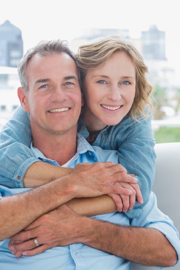 Mulher feliz que abraça seu marido no sofá de atrás fotografia de stock