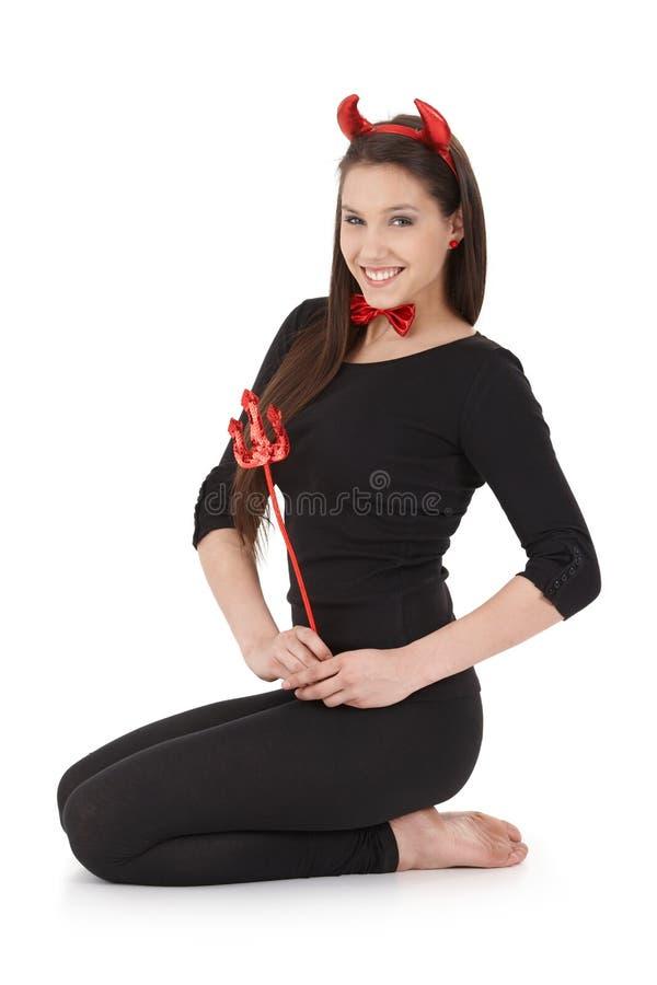 Mulher feliz que ajoelha-se no traje do diabo imagens de stock
