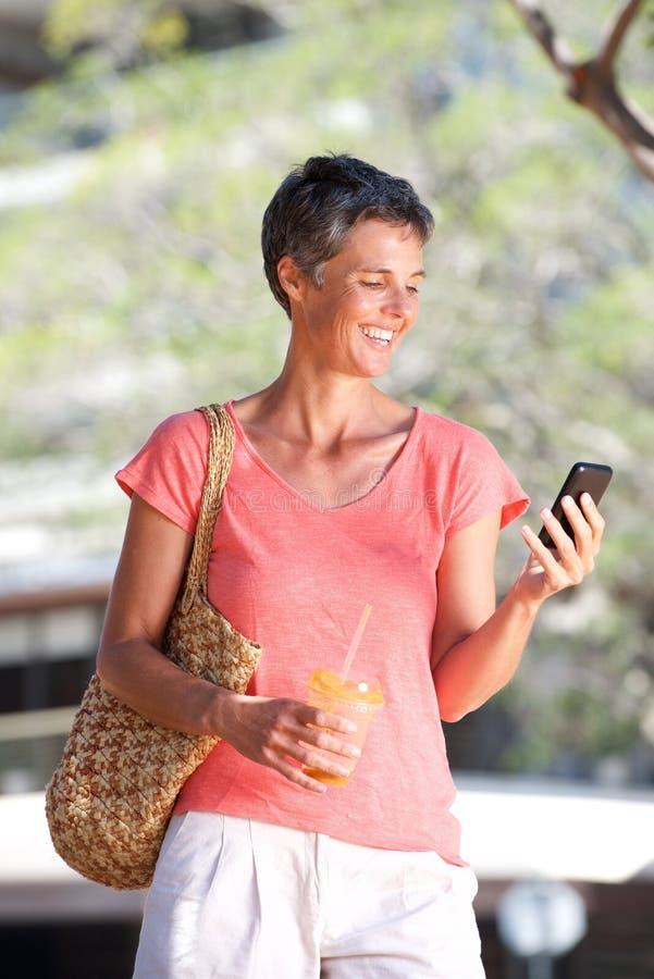 Mulher feliz que anda fora com bebida e telefone celular imagens de stock royalty free