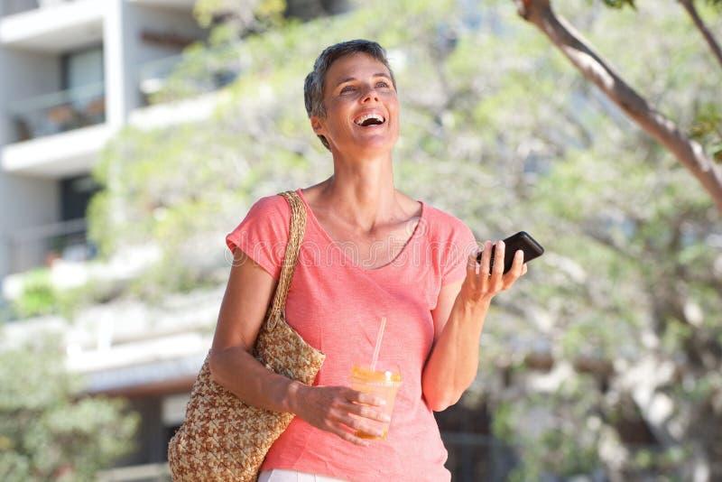 Mulher feliz que anda fora com bebida e telefone celular imagem de stock
