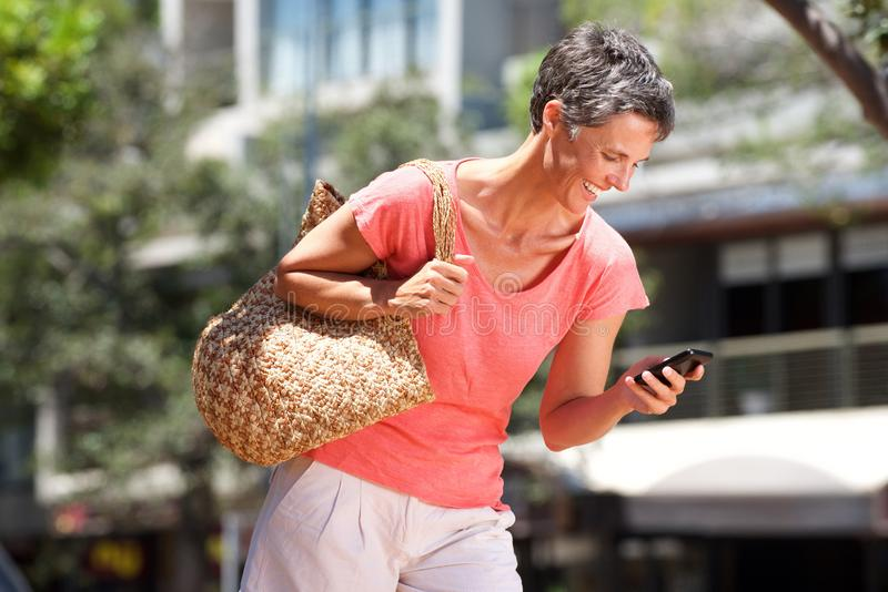 Mulher feliz que anda fora com telefone celular imagens de stock