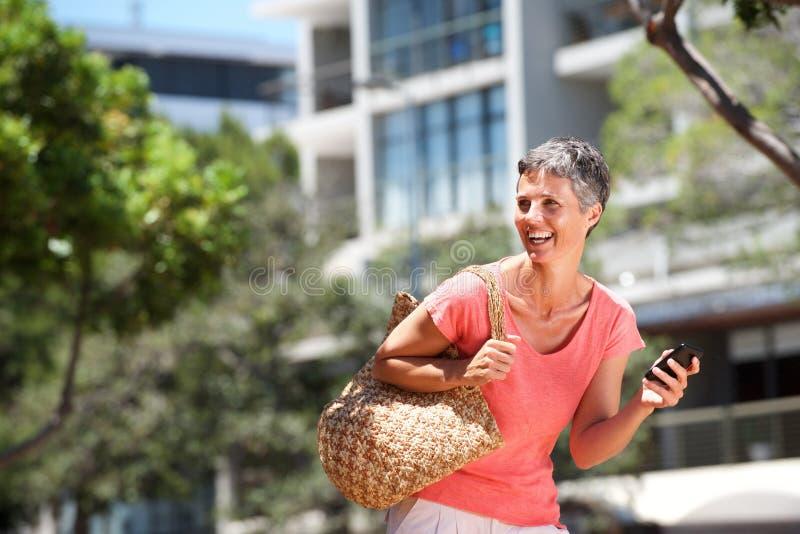 Mulher feliz que anda fora com telefone celular fotografia de stock royalty free