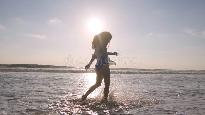 Mulher feliz que anda na praia do oceano e que pulveriza a água com seus pés Menina bonita nova que aprecia a vida foto de stock royalty free