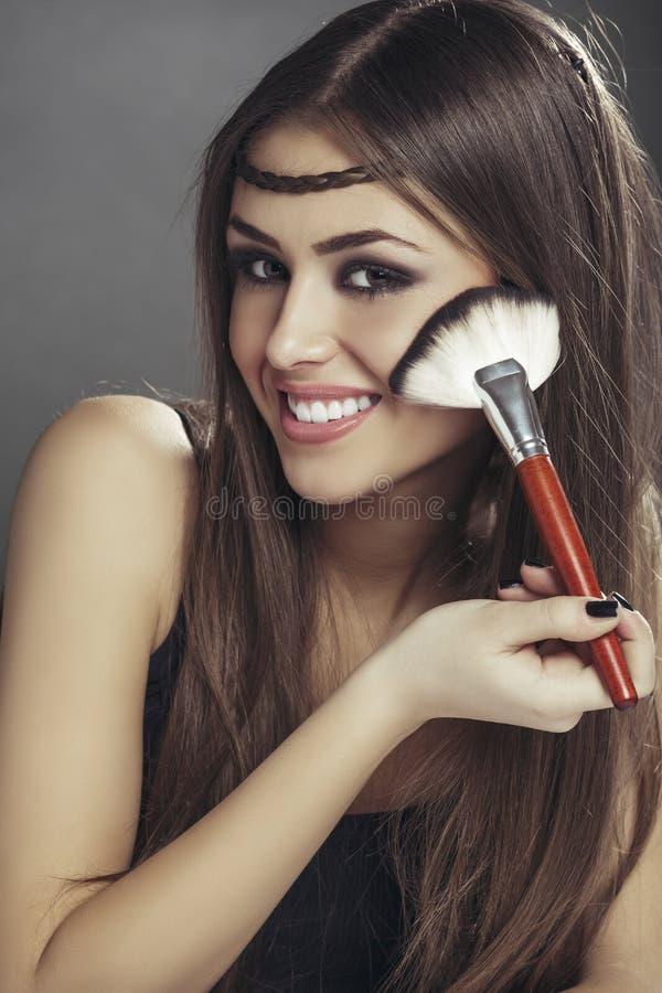 Mulher feliz que aplica a composição em sua cara imagem de stock