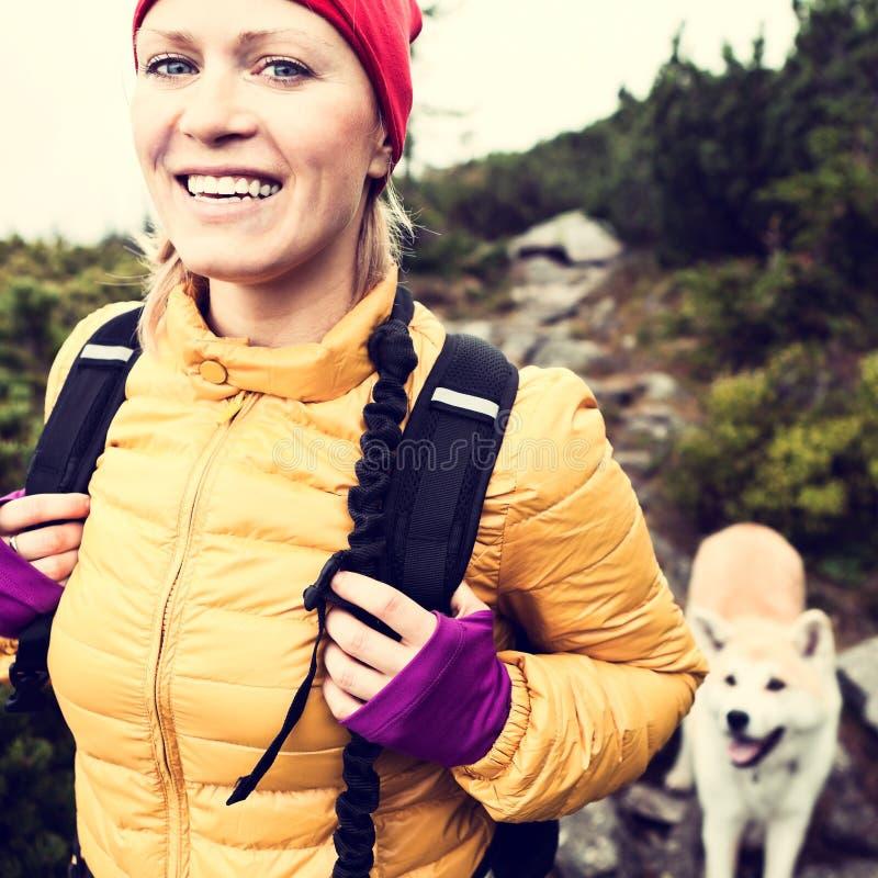Mulher feliz que caminha em montanhas do vintage com cão foto de stock royalty free