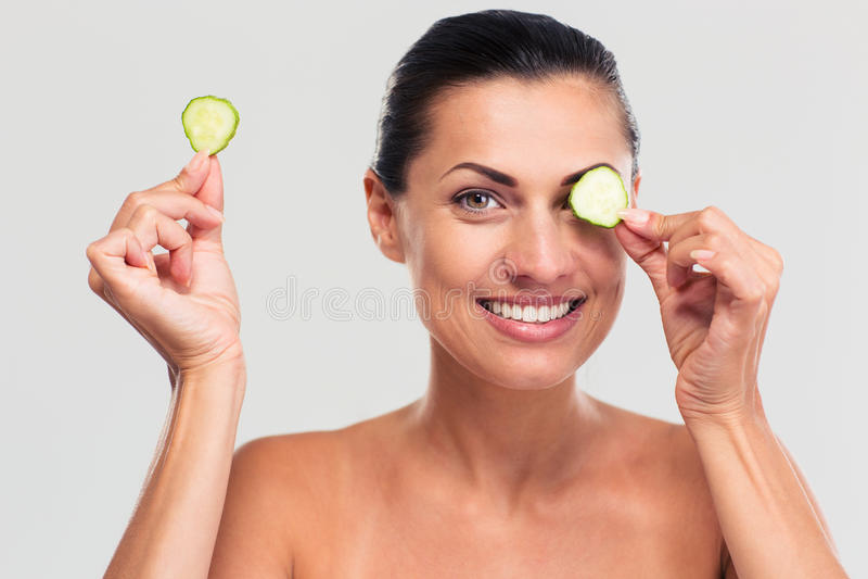 Mulher feliz que cobre seu olho com o pepino foto de stock royalty free