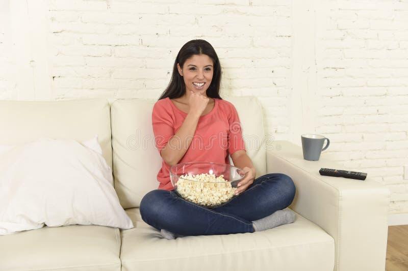 Mulher feliz que come a televisão de observação da pipoca no filme de apreciação entusiasmado feliz do sofá do sofá imagem de stock