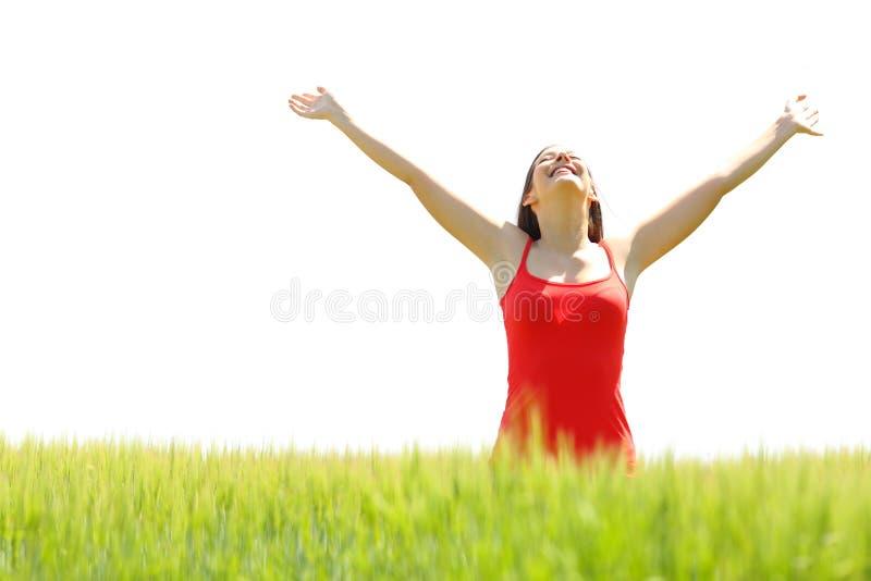 Mulher feliz que comemora o sucesso que aumenta os braços em um campo imagem de stock
