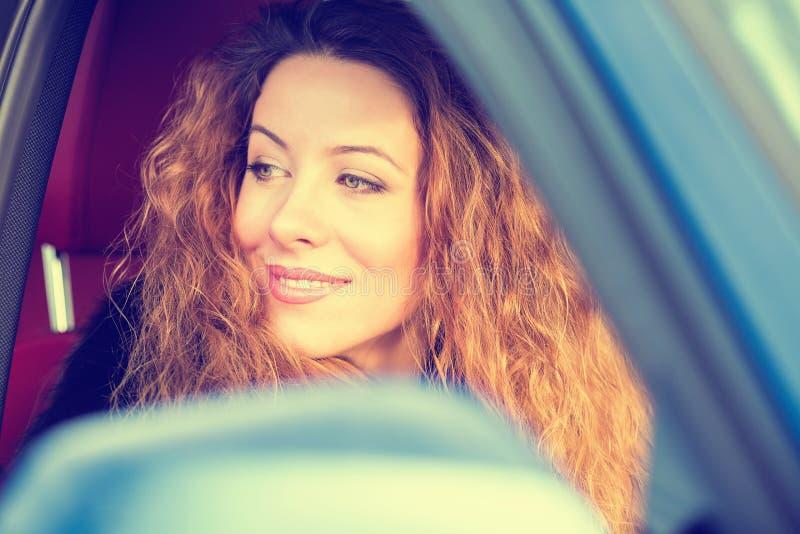 Mulher feliz que conduz no carro no dia ensolarado bonito da viagem por estrada fotografia de stock