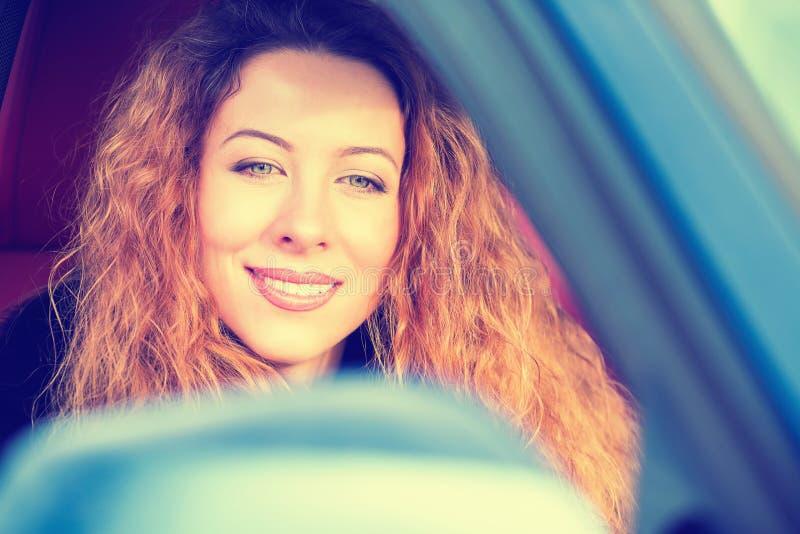 Mulher feliz que conduz no carro no dia ensolarado bonito da viagem por estrada imagem de stock