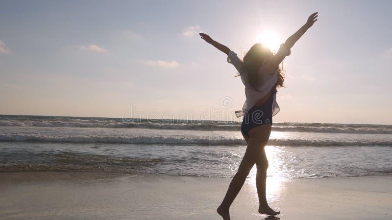 Mulher feliz que corre e que gira na praia perto do oceano Menina bonita nova que aprecia a vida e que tem o divertimento no mar fotos de stock royalty free