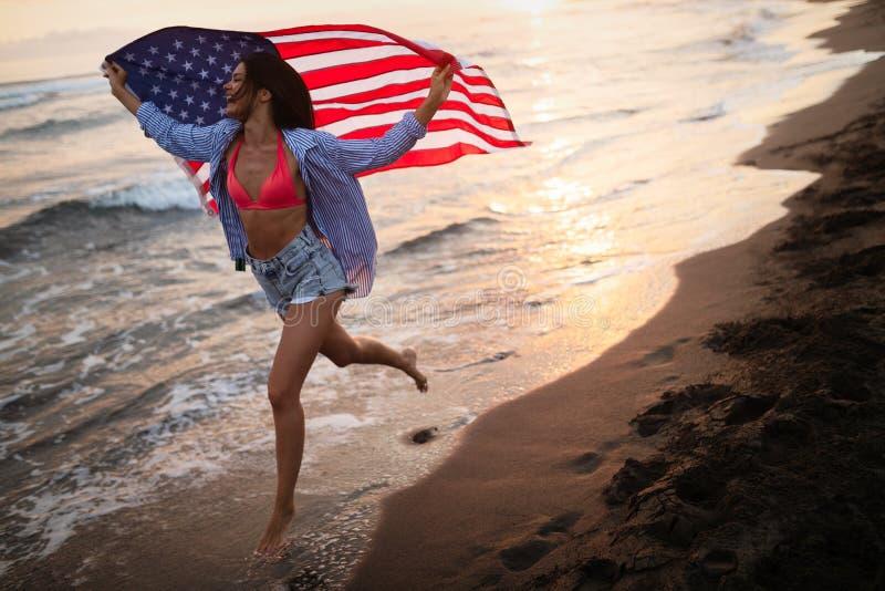 Mulher feliz que corre na praia ao celebrateing o Dia da Independ?ncia e ao apreciar a liberdade nos EUA foto de stock royalty free