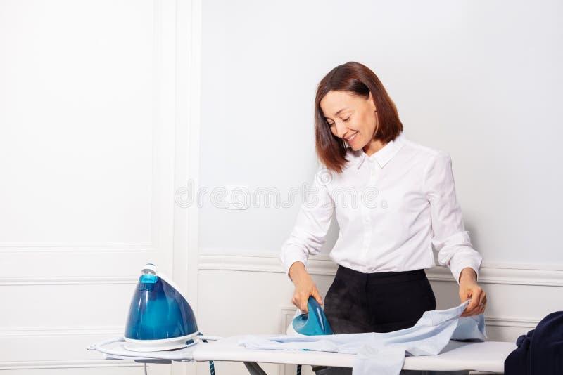 Mulher feliz que cozinha a camisa antes de sair para o trabalho imagens de stock royalty free