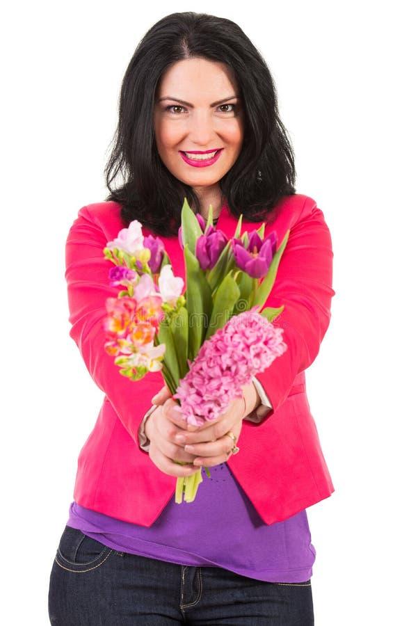 Mulher feliz que dá flores da mola imagem de stock