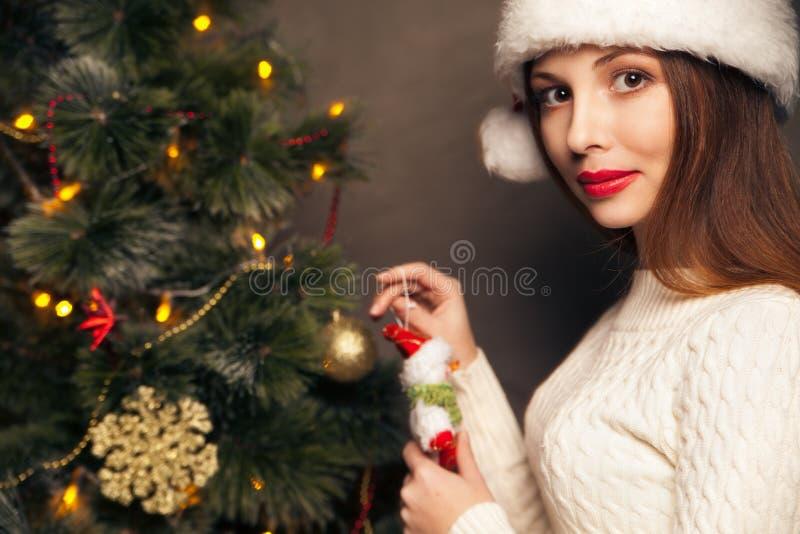 Mulher feliz que decora uma árvore de Natal fotografia de stock royalty free