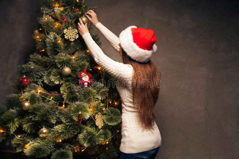 Mulher feliz que decora uma árvore de Natal fotografia de stock
