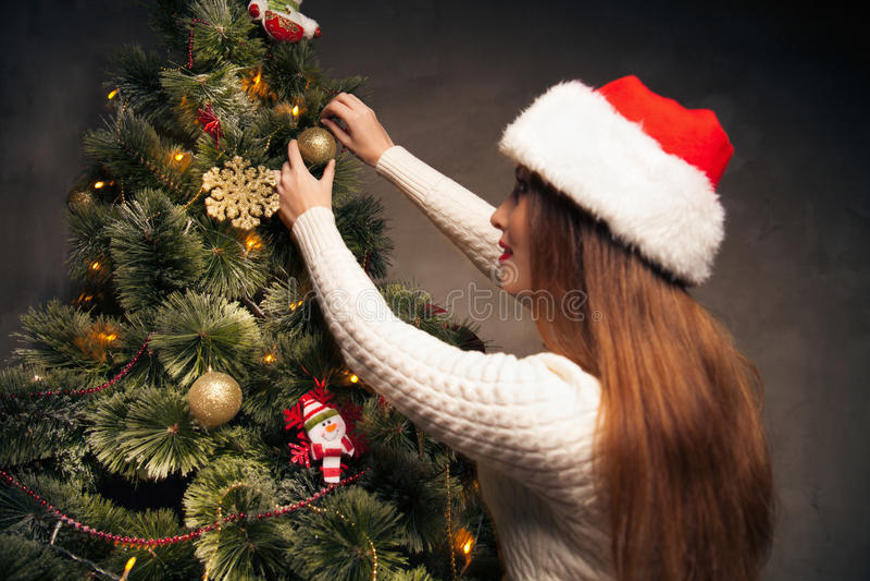 Mulher feliz que decora uma árvore de Natal foto de stock