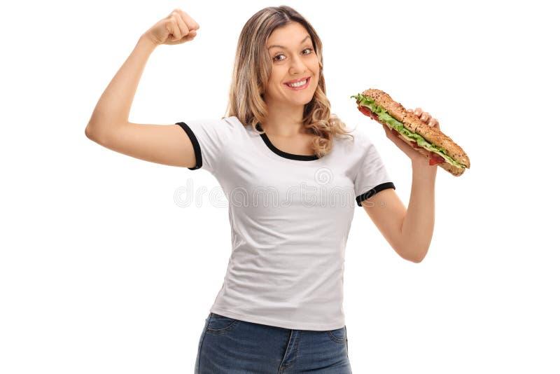 Mulher feliz que dobra seu bíceps e que guarda um sanduíche imagens de stock