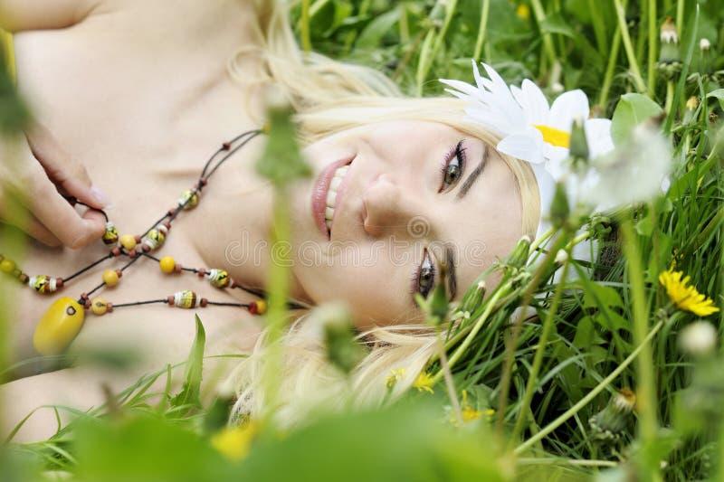 Mulher feliz que encontra-se no campo com camomiles. imagens de stock royalty free