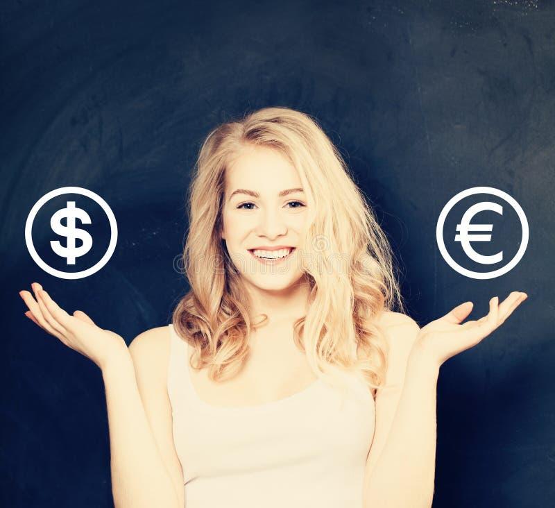 Mulher feliz que escolhe a moeda do dólar dos EUA ou do Euro do ES no fundo do quadro-negro, conceito dos investimentos imagens de stock