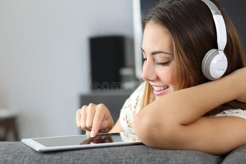 Mulher feliz que escuta a música de uma tabuleta em casa foto de stock