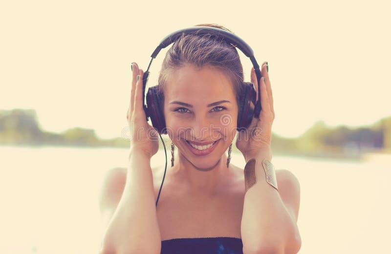 Mulher feliz que escuta a música em fones de ouvido fora pelo lago imagens de stock