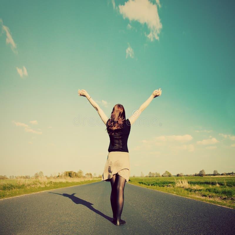 Mulher feliz que está na estrada vazia. Estilo retro do vintage fotografia de stock