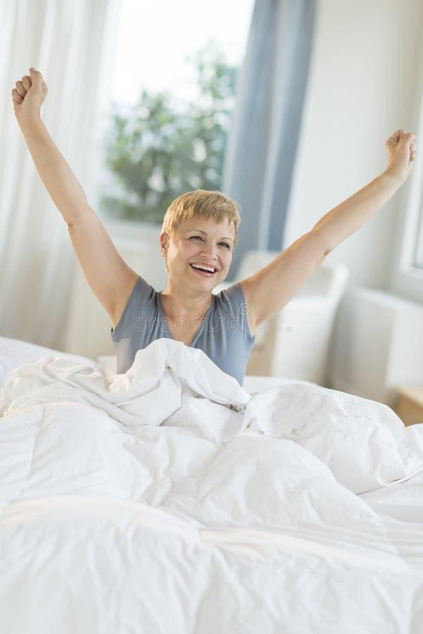 Mulher feliz que estica na cama fotos de stock royalty free