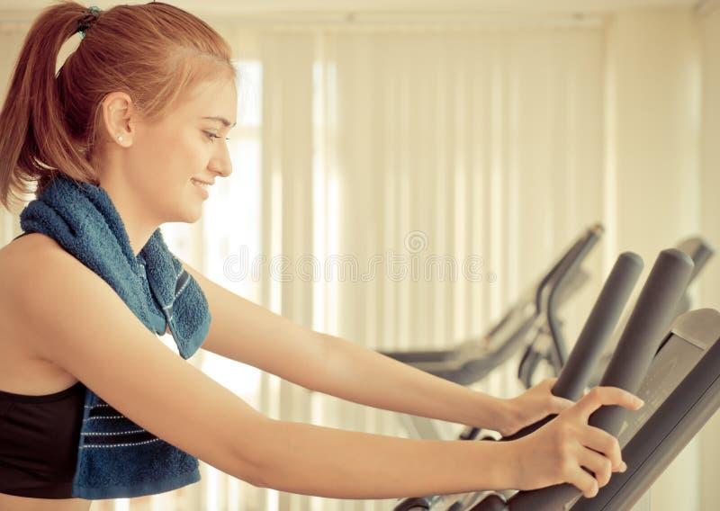 Mulher feliz que exercita em uma máquina da bicicleta da aptidão foto de stock