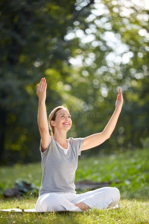 Mulher feliz que faz a ioga na natureza fotos de stock