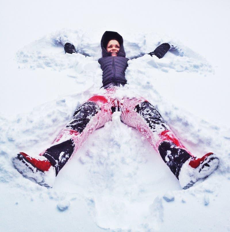 Mulher feliz que faz o anjo da neve imagem de stock