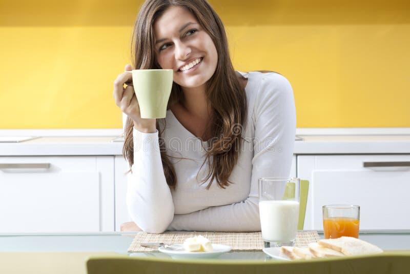 Mulher feliz que faz o pequeno almoço fotografia de stock