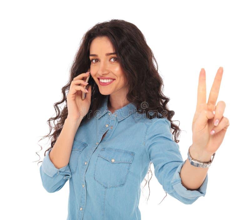 Mulher feliz que faz o sinal da vitória ao falar no telefone imagem de stock