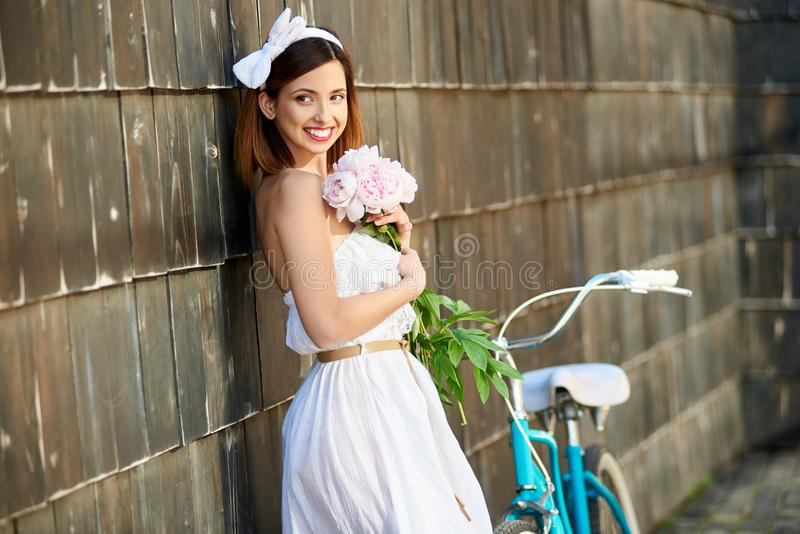 Mulher feliz que guarda as peônias que inclinam-se contra a parede e o sorriso fotos de stock