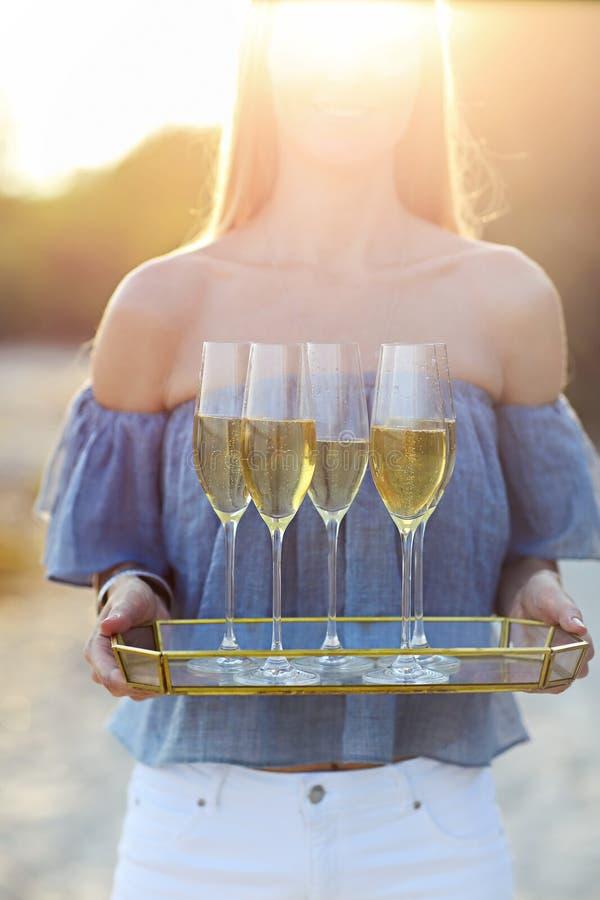 Mulher feliz que guarda a bandeja com vinho espumante do champanhe em glas imagem de stock royalty free