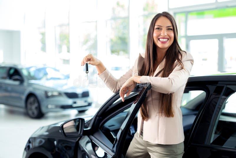Mulher feliz que guarda chaves a seu carro novo no negócio imagens de stock royalty free
