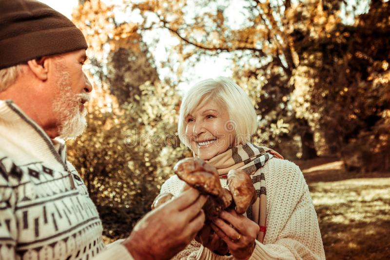 Mulher feliz que guarda cogumelos e que olha seu marido imagens de stock