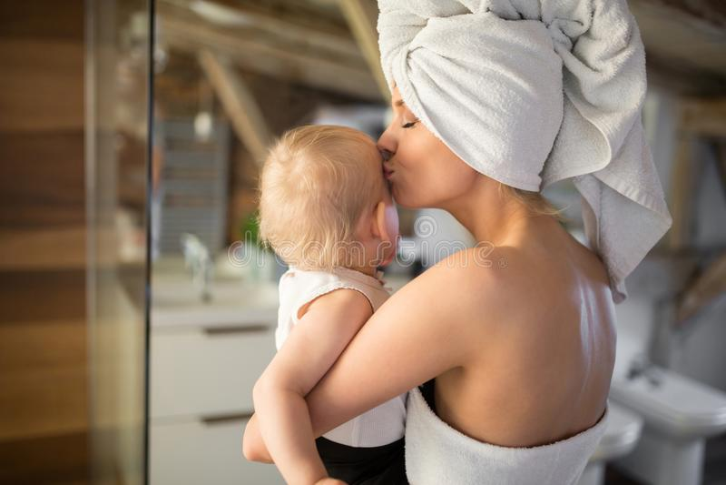 Mulher feliz que guarda e que beija o bebê foto de stock